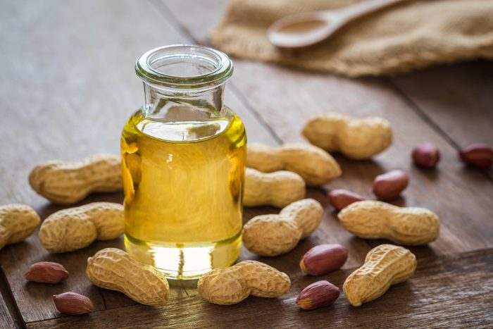 healthiest cooking oils   Peanut oil in glass bottle and peanuts