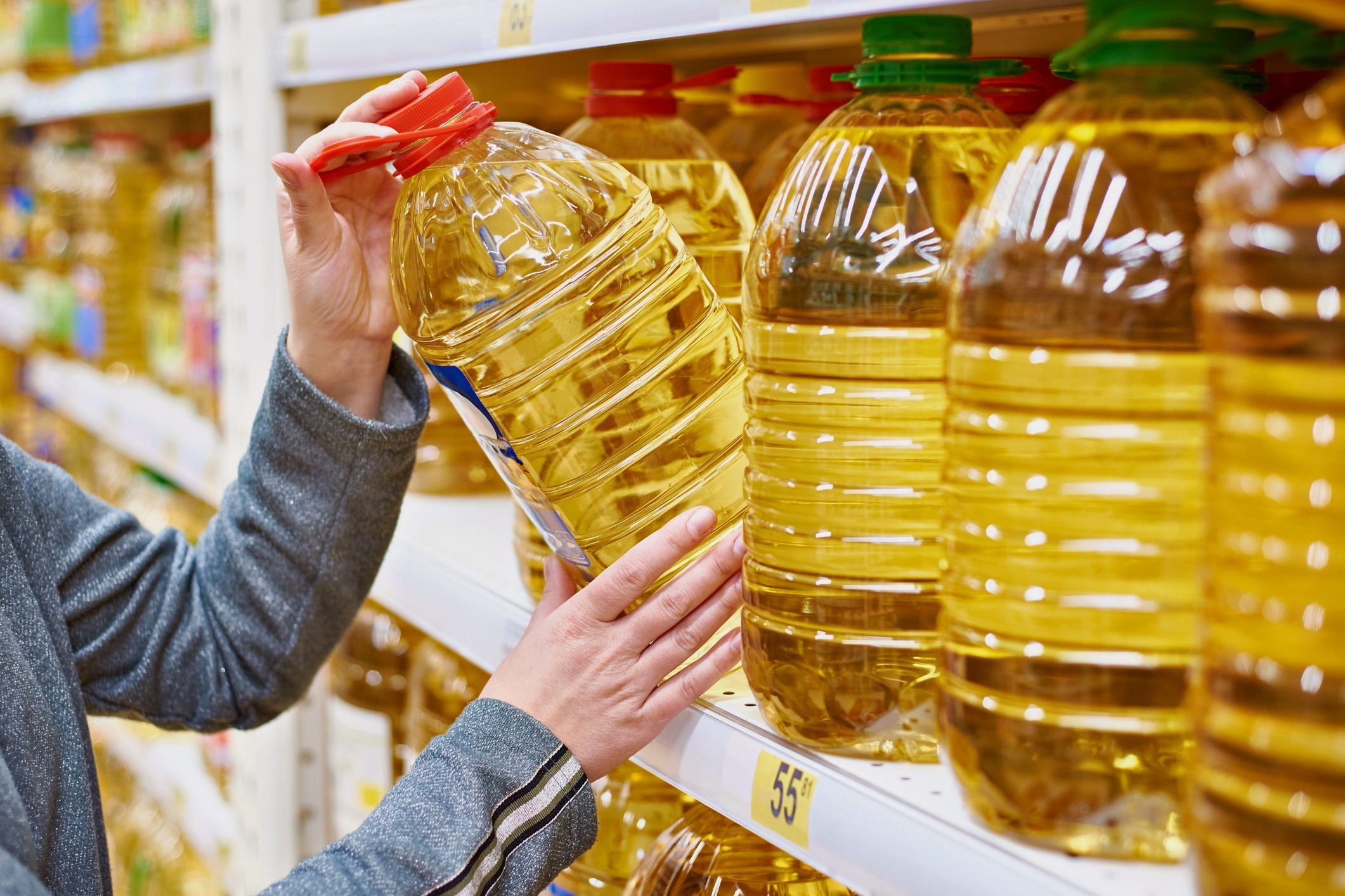canola oil vs vegetable oil| Confused about the difference between canola and vegewoman taking large bottle of oil off of shelf at grocery store
