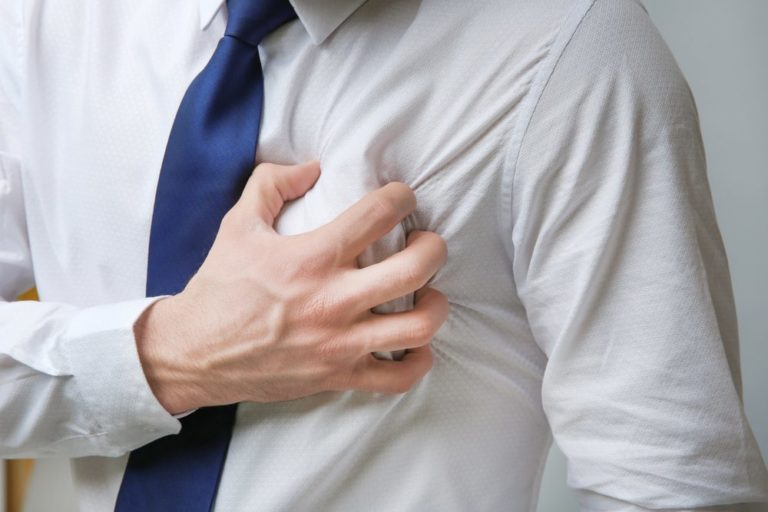 Heart attack concept. Young man suffering from chest pain, close up