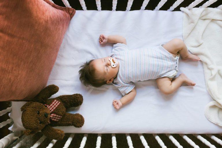 Adorable newborn lies in the crib