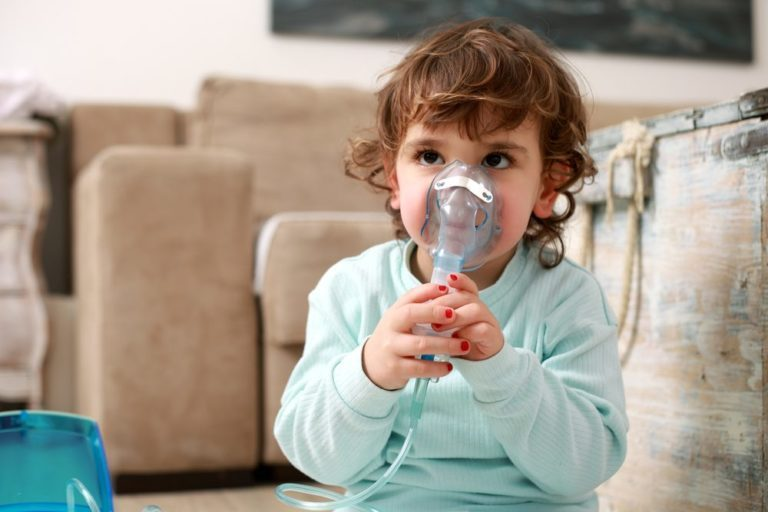 Little girl with asthma problems or allergy using inhaler at home