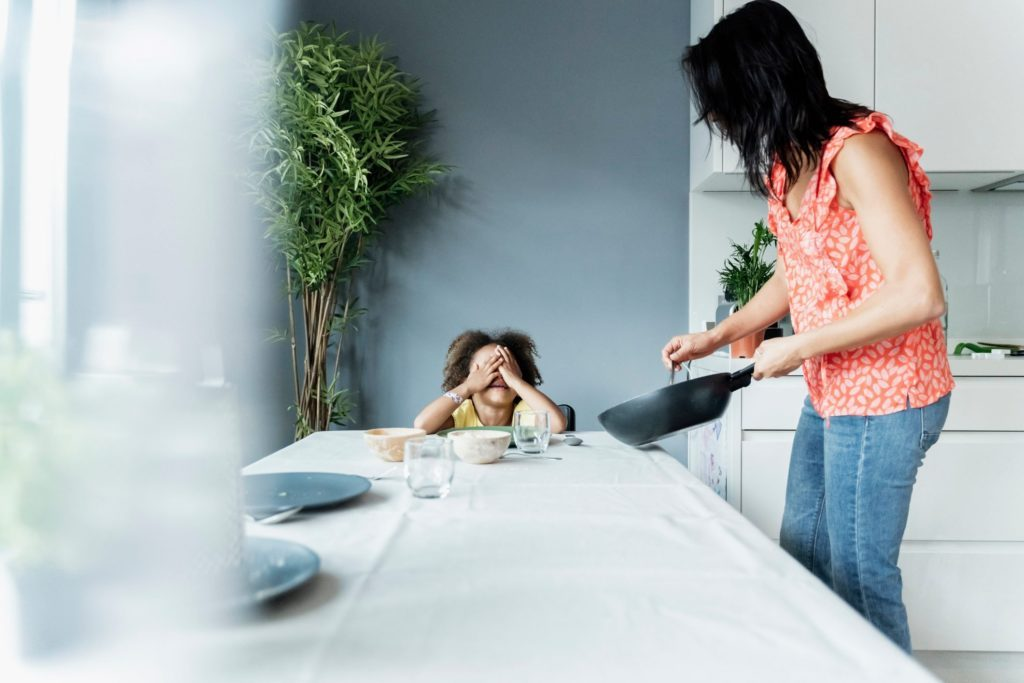 disordered eating triggers kids   Mother serving meal for daughter sitting at dining table
