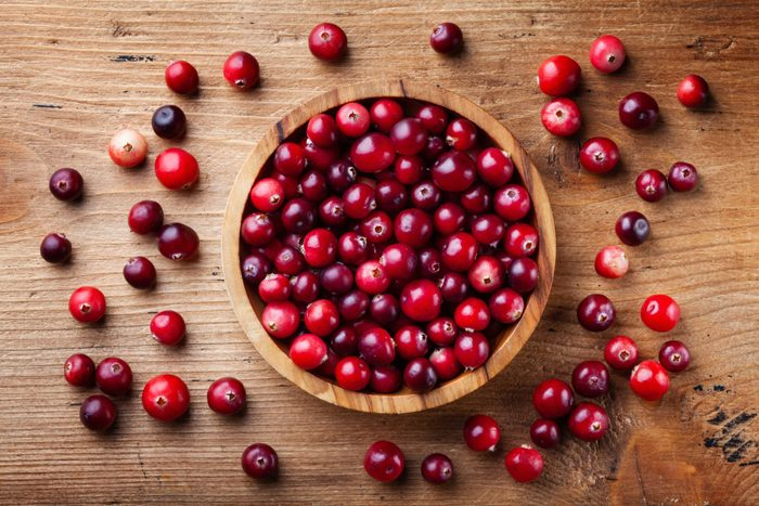cranberry health benefits | Fresh raw cranberry in wooden bowl on rustic table top view.