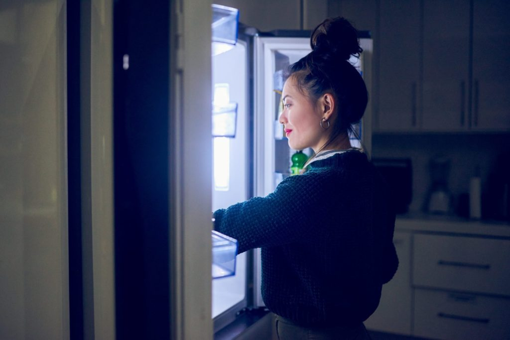 healthy late night snacks | woman opening the fridge at night
