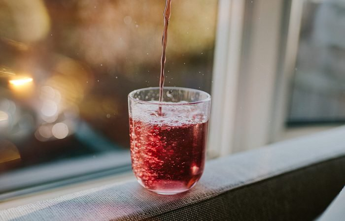 pouring glass of red soda