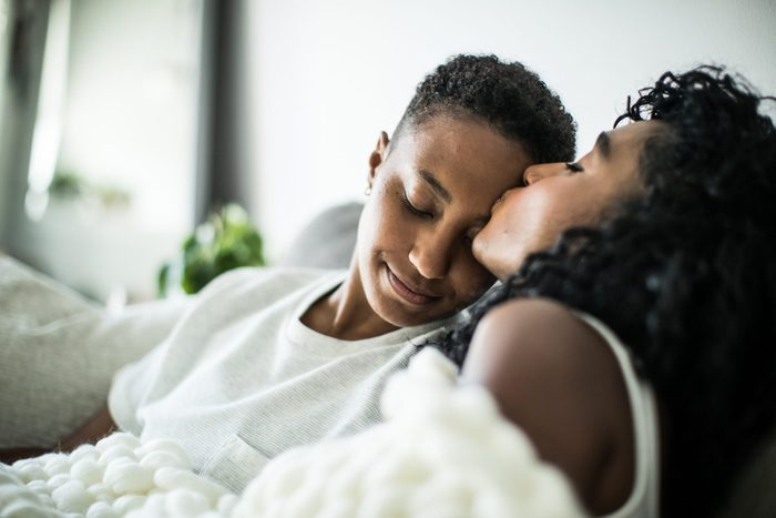 Lesbian couple at home snuggling under blanket
