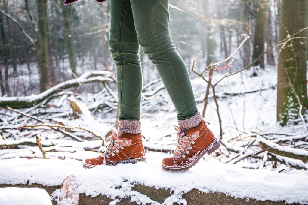 womens hiking footwear| A woman hiking in the forest at the snowstorm
