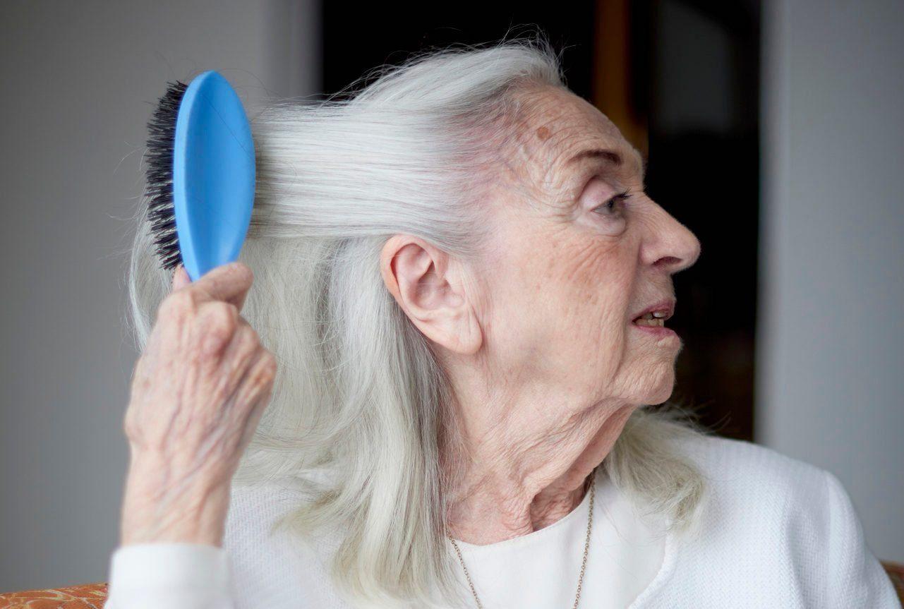 Older Caucasian woman brushing hair