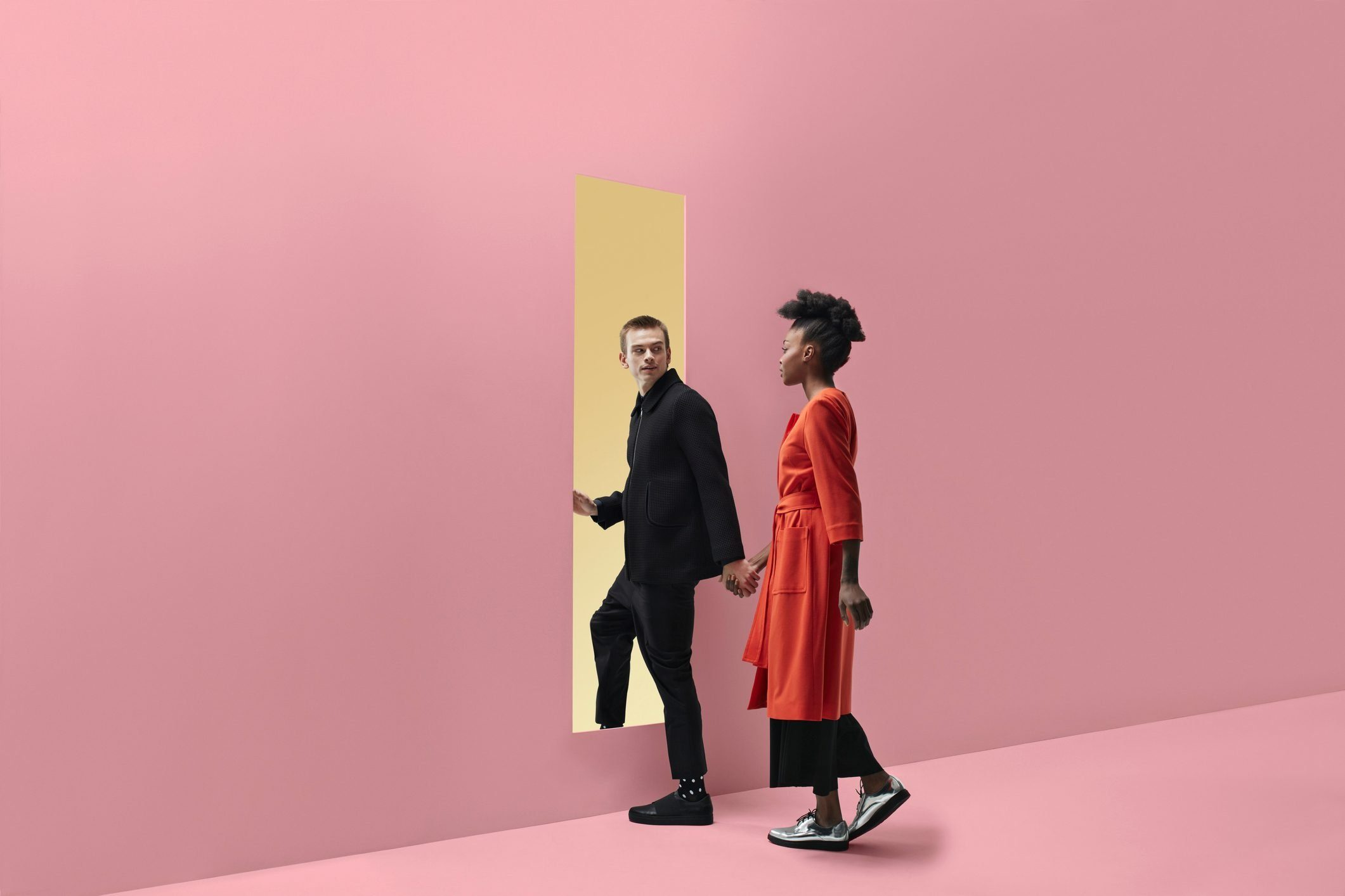 signs you're dating a narcissist | Woman & man holding hands, approaching rectangular opening in coloured wall