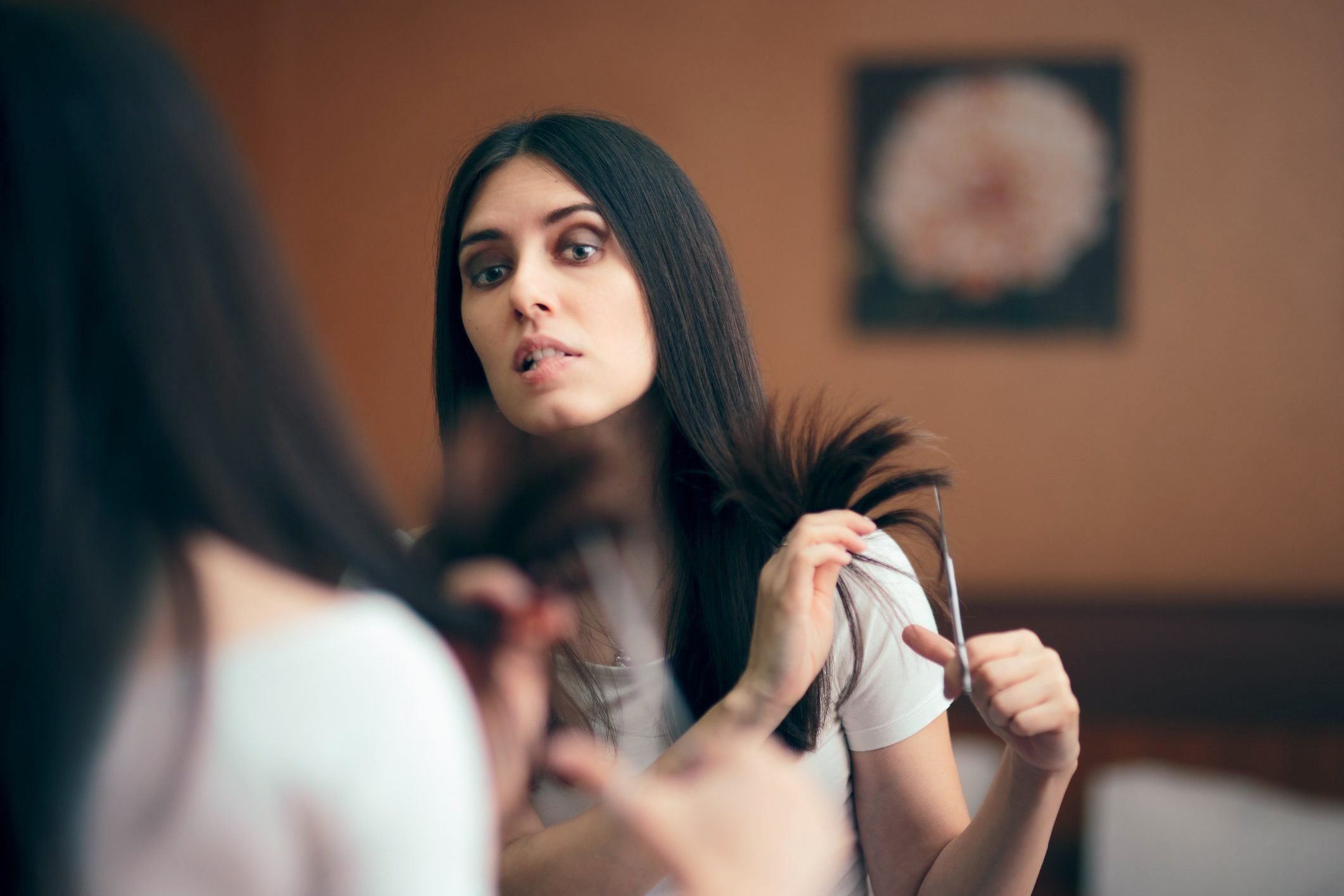 Woman Looking in Mirror Cutting Split Hair Ends