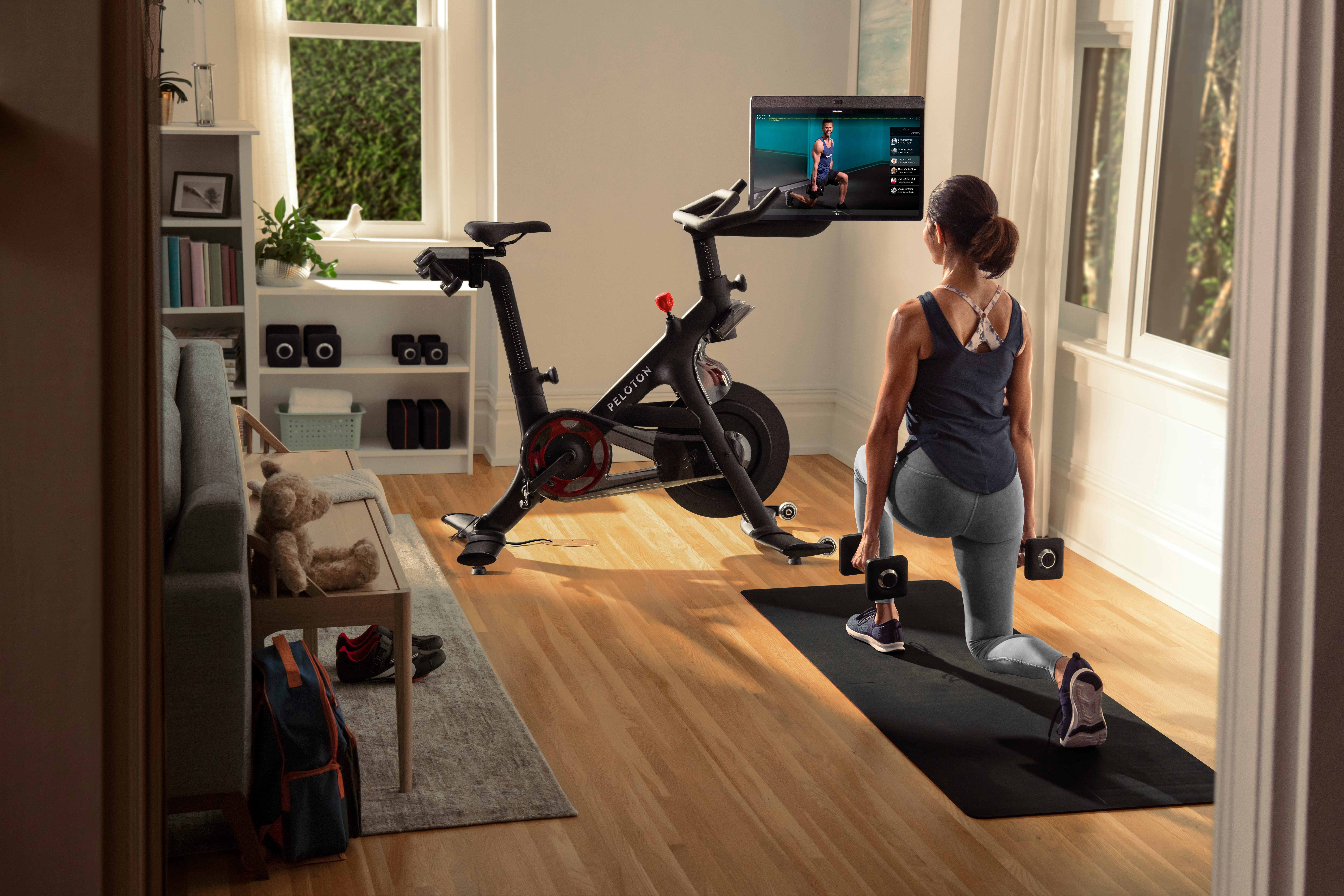 peleton bike+ review canada | image of the peleton with woman doing floor exercises next to it