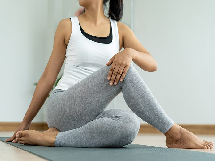 pelvic floor health | woman sitting on a yoga mat stretching her hips