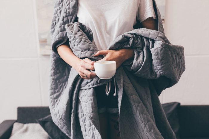 weighted blankets benefits | woman holding a blanket around her body | weighted blankets anxiety