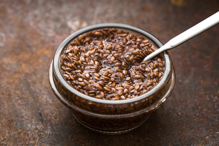 Bowl with flax seeds in water on metal background horizontal