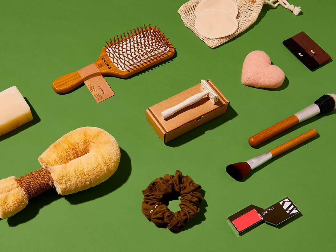 best sustainable beauty tools | flat lay of sustainable beauty tools on a green background