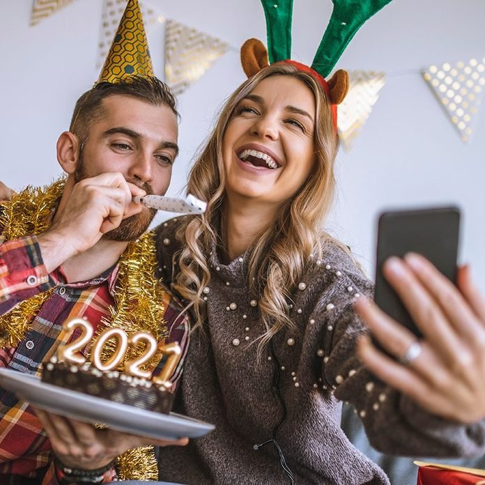 how to host a virtual new years party | Couple celebrating Christmas at home, holding chocolate cake with lit candles shaped as numbers 2021 and having a video call with friends