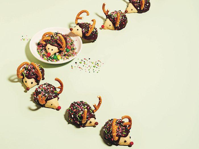 kim-joy christmas cookies   little hedgehog cookies arranged to look like they're marching through sprinkles