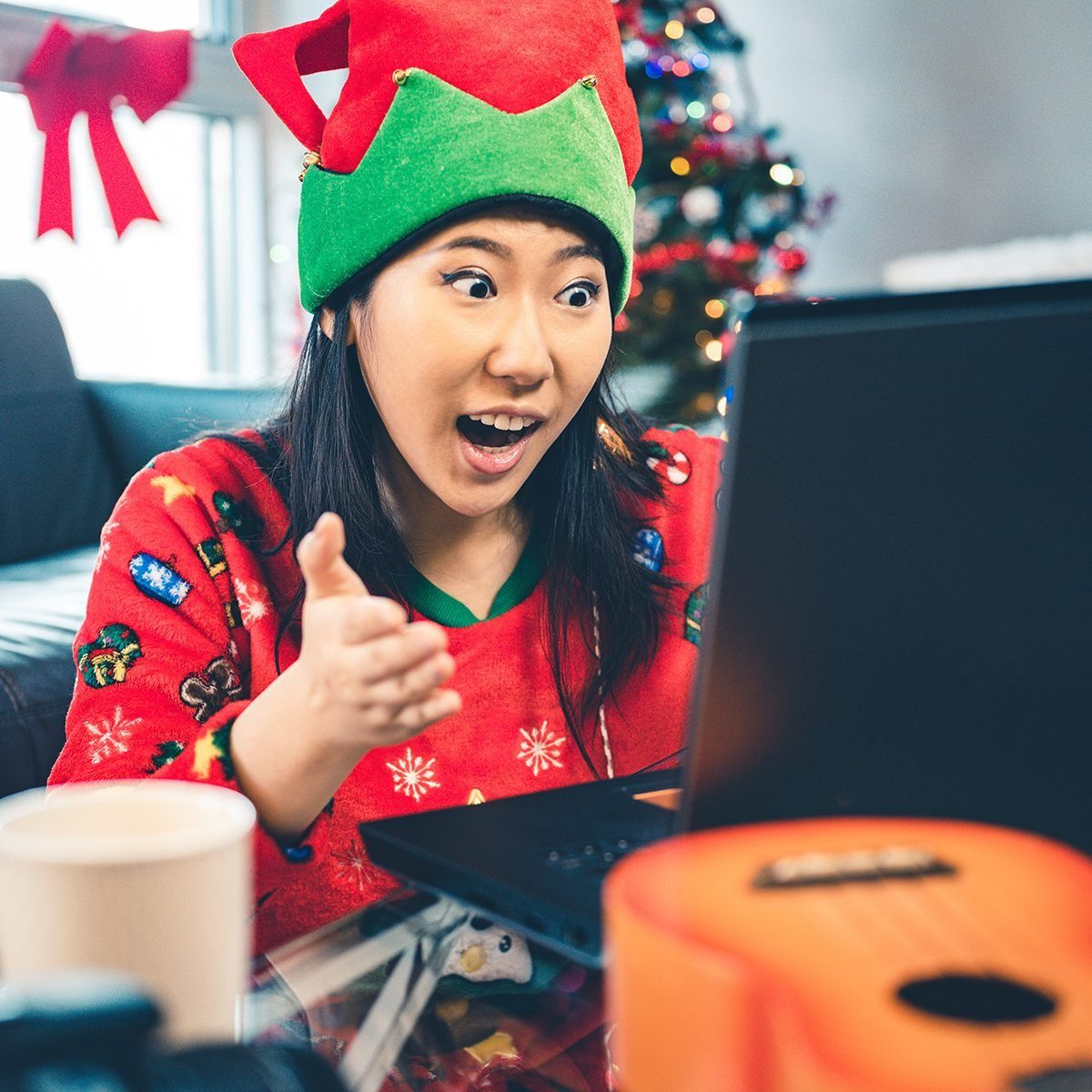 Millennial Christmas party in season costumes. Interior of modern apartment with Christmas decorations. Portrait of a young Chinese woman looking at laptop