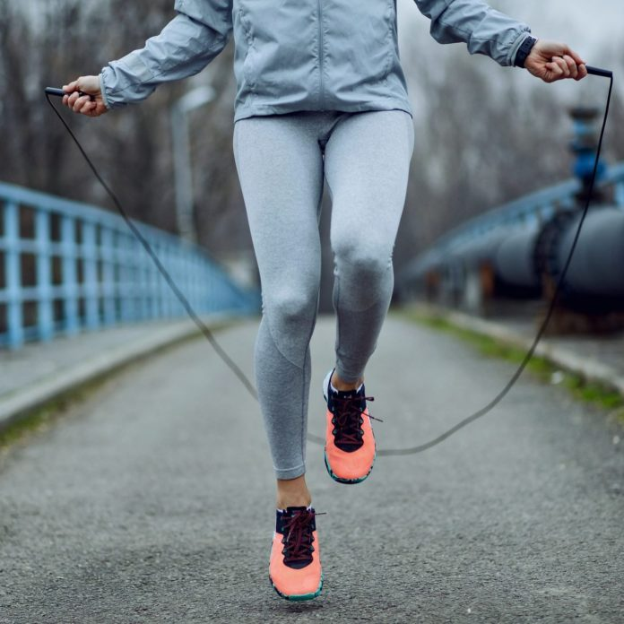 Unrecognizable Sportswoman Jumping Rope On A Bridge