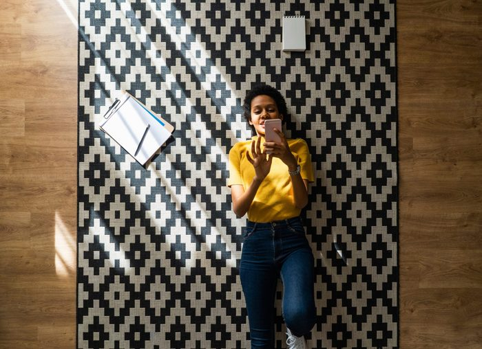 self care plan | Young woman lying on carpet at home using smartphone