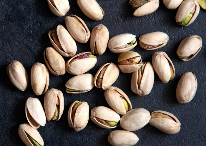 are pistachios good for you?   Roasted pistachios nuts on dark background. Healthy snack