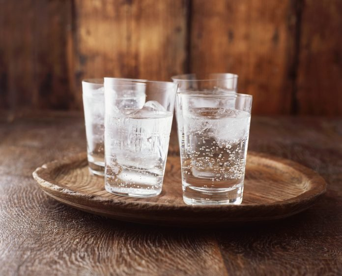 Sparkling water in drinking glass with ice on vintage wooden plate