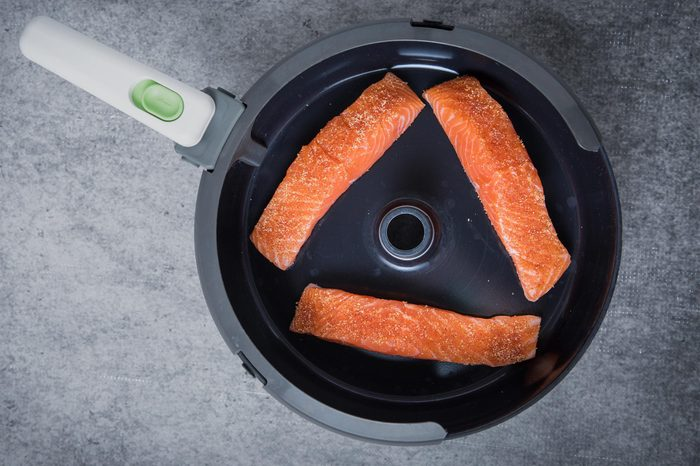 Three pieces of raw salmon in the air fryer at the center with a grey background. Air frying fish. Air frying salmon for a healthy salmon meal. Uncooked salmon in a pan shot in the center.