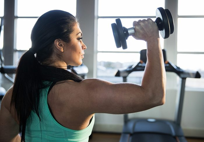 how to get stronger arms   strong woman ddoing a shoulder press with dumbbell
