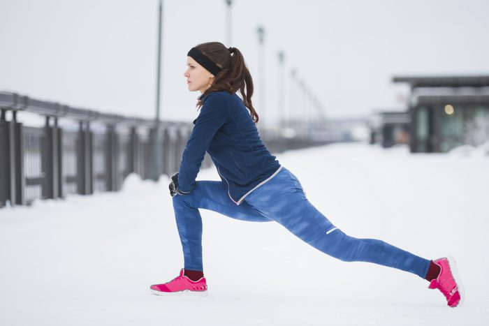 thermal leggings | woman stretching in the snow