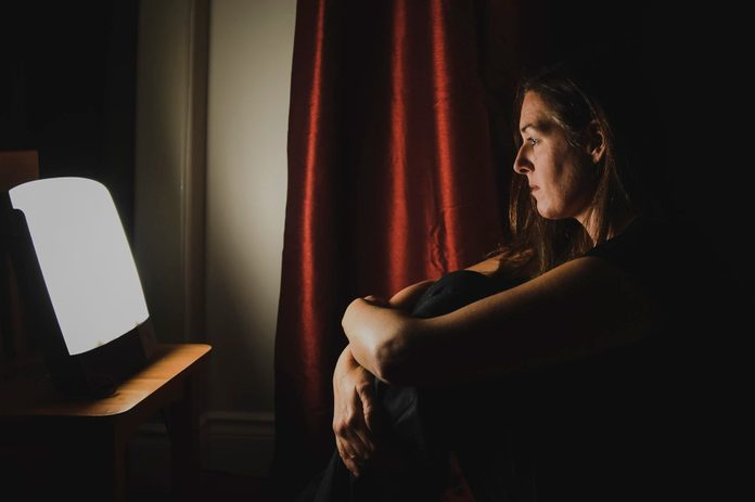 light therapy | Profile Of Woman Sitting Looking At Light Therapy Lamp In A Dark Room