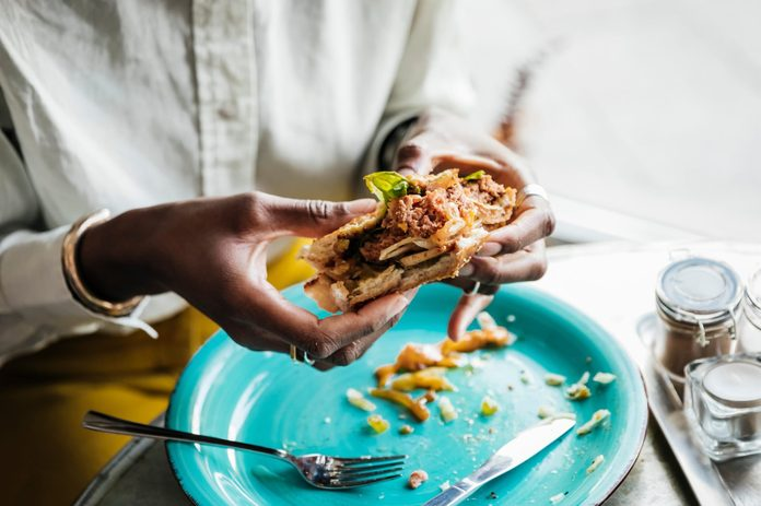 Woman Eating Tasty Vegan Burger