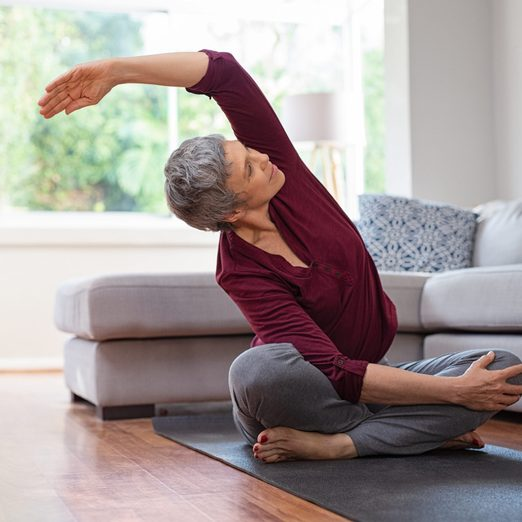stretches for back pain | Senior,woman,exercising,while,sitting,in,lotus,position.,active,mature