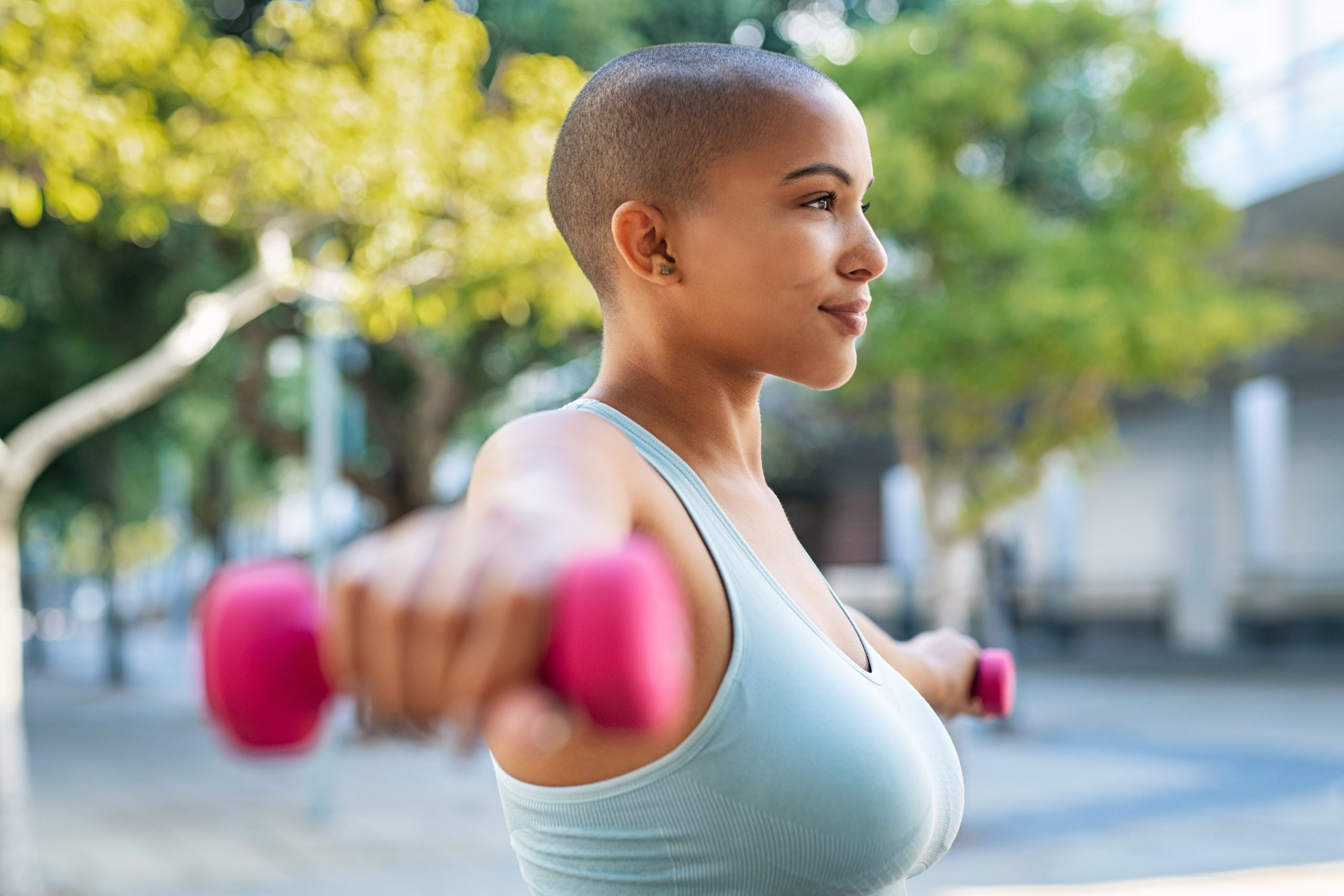 shoulder pain exercise   Active woman,using,dumbbells,in,the,park.,side,view