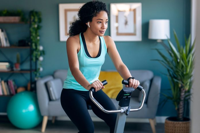 spin bikes canada | Shot,of,sporty,african,young,woman,exercising,on,smart,stationary