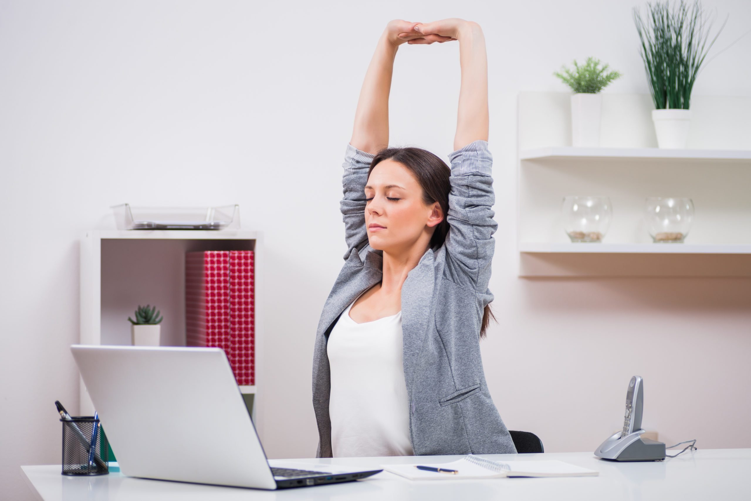 Young,businesswoman,is,relaxing,in,her,office.,she,is,stretching