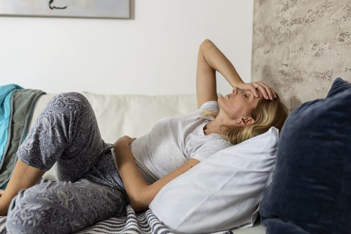 ulcerative colitis vs crohns disease | Mature Woman Lying On The Bed Suffering From Stomachache And Painful Period Cramps