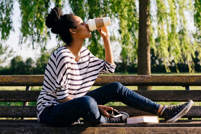 Young Woman Sitting On Park Bench Drinking Coffee To Go