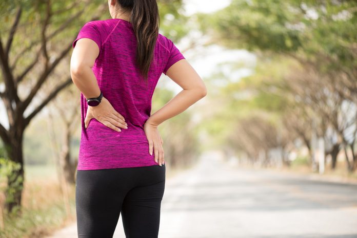 hip pain running | woman clutching painful hip while running