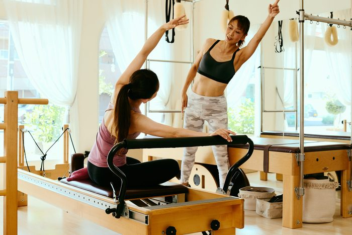 pilates benefits | Senior Woman Pilates Instructor Leading Class On Pilates Reformers In Fitness Studio