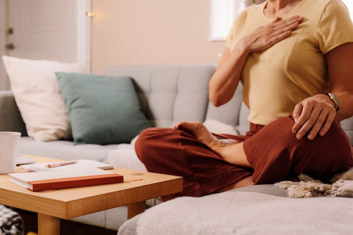 daily meditation | Woman Indoors Relaxing Meditating And Doing Breathing Exercises