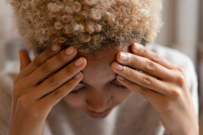 migraine triggers | Woman With Headache Rubbing Forehead