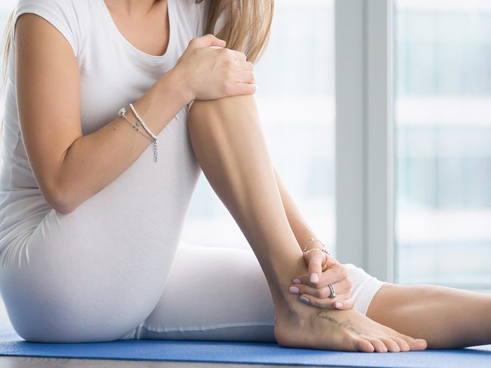 ankle stretches   how to stretch ankles   young,woman,sitting,on,the,mat,,grabbing,an,ankle,