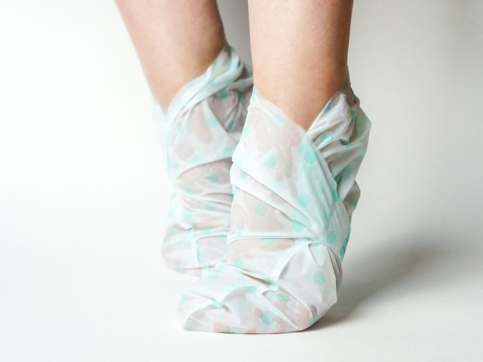 The,girl,puts,on,a,moisturizing,foot,mask,,for,dry