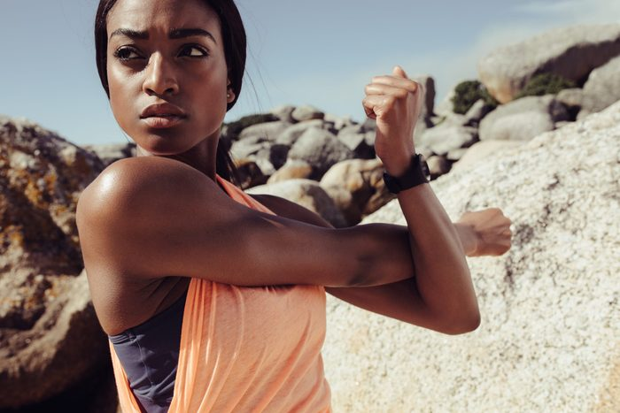 African,woman,stretching,arms,at,the,beach.,fitness,female,doing