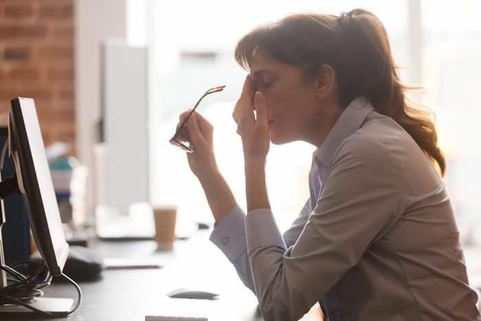 Exhausted,female,worker,sit,at,office,desk,take,off,glasses