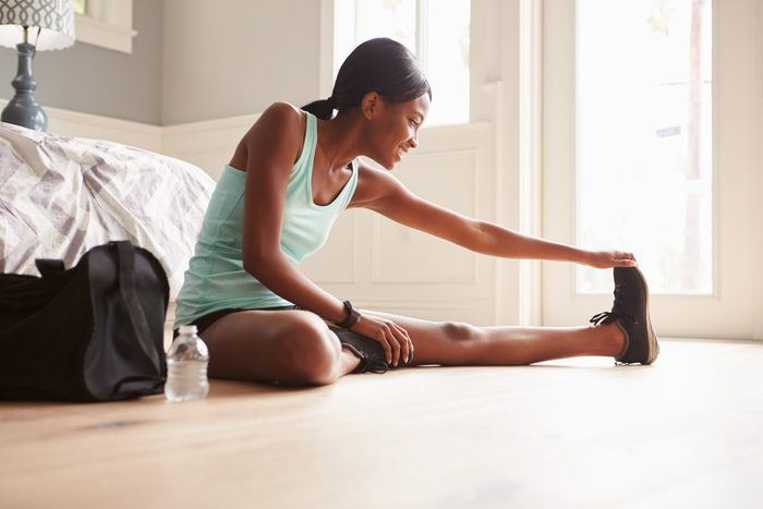 Young,black,woman,sitting,on,the,floor,at,home,stretching