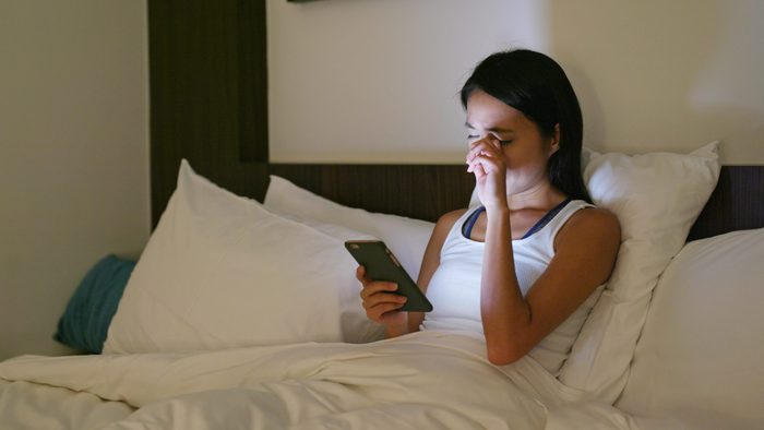 what is dry eye   woman rubbing her eyes while using cellphone in bed