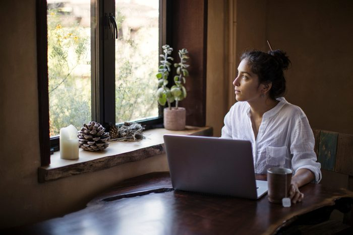 Mixed Race Young Adult Woman Works At Home Using Laptop Computer