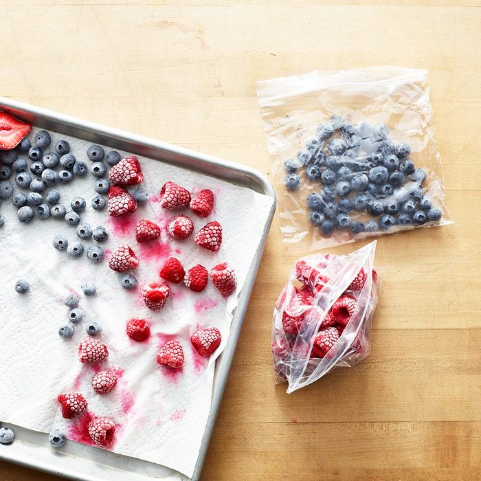 how to make frozen drinks Overhead of freezing berry preparation, rasperries, blueberries and strawberries sit frozen on a paper towel on a silver baking sheet with plastic bags holding more frozen berries sitting next to the tray on a wooden surface.