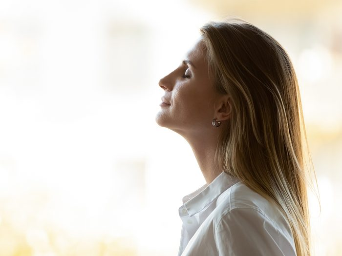 Calm,happy,business,woman,breathing,fresh,air,standing,at,window,